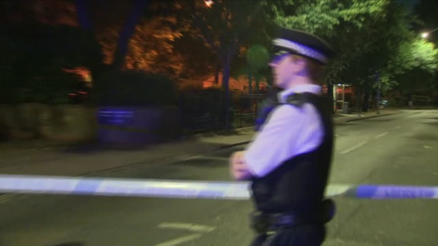 vídeos de stock e filmes b-roll de exterior night shots of police officers on guard and stood next to police cordon tape including shots of a vehicle at the crime scene where a man was... - peckham