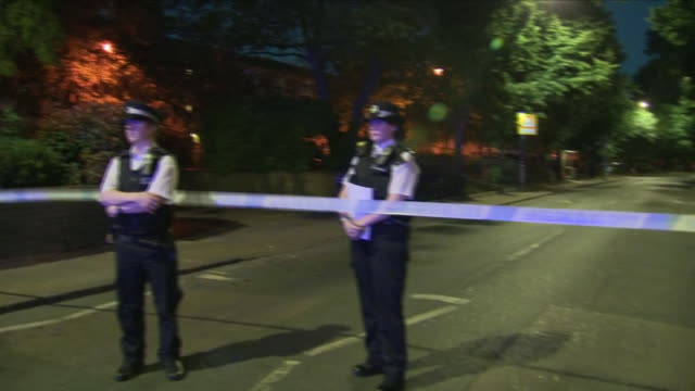 vídeos de stock e filmes b-roll de exterior night shots of police officers stood on guard by police cordon tape at the crime scene where a man was shot in his face on 2nd june 2018 in... - peckham