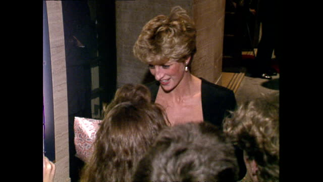 exterior night shots of princess diana princess of wales receiving flowers from fans before getting into car as she departs sadler's wells theatre on... - イズリントン点の映像素材/bロール