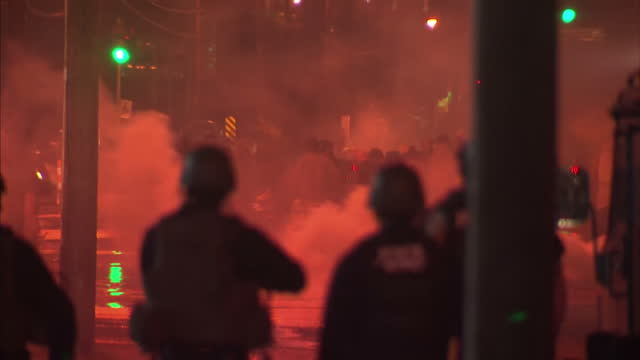Exterior night shots of protesters covering their faces against tear gas one picks up a tear gas canister and throws it back towards the police A...