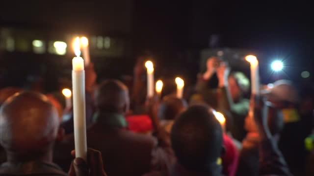 exterior night shots of protesters holding candles and singing outside of court room after pastor evan mawarire is freed on july 13 2016 in harare... - pastor stock videos & royalty-free footage
