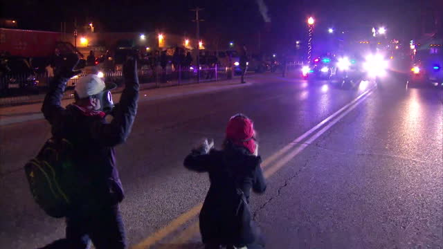 exterior night shots of protesters kneeling in the street in front of a convoy of police vehicles with audio of a police officer warning protesters... - manifestante video stock e b–roll