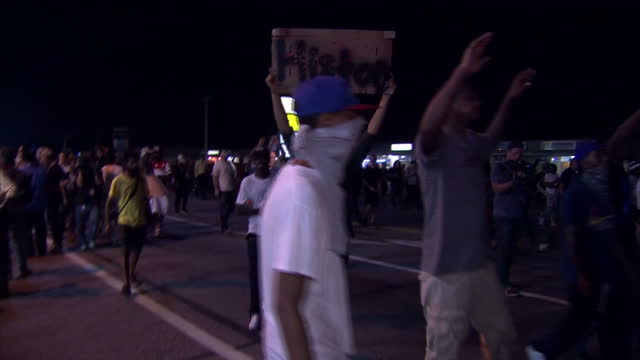 exterior night shots of protesters marching through ferguson many with their hands held up and chanting 'hands up don't shoot'>> on august 19 2014 in... - missouri stock videos & royalty-free footage
