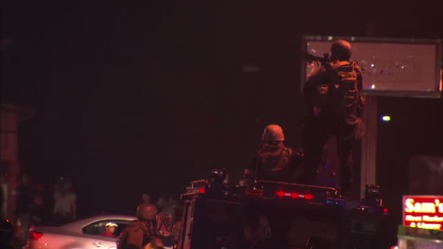 Exterior night shots of riot police standing in the street with one appearing to throw tear gas towards an unseen target An armed police officer...