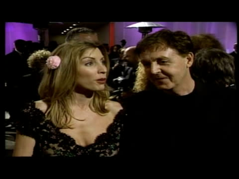 vídeos y material grabado en eventos de stock de exterior night shots of sir paul mccartney and heather mills speaking to reporters as they arrive at the vanity fair post oscars party - 2002