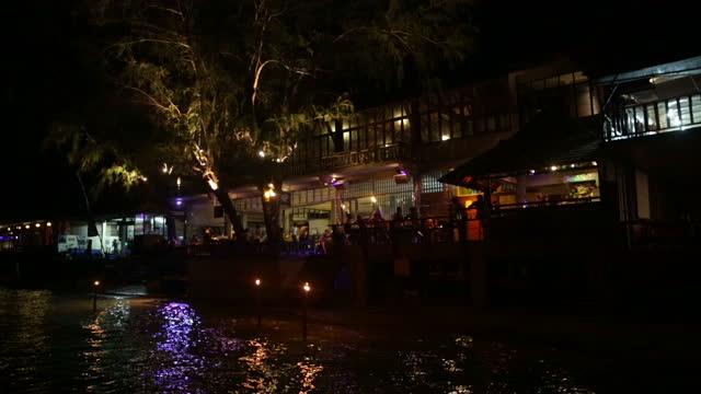 vídeos y material grabado en eventos de stock de exterior night shots of tourists drinking at a beachfront bar on koh tao island as a musician plays guitar and sings note audio is mute to avoid... - instrumento de cuerdas