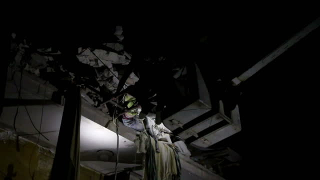Exterior night shots of volunteers from the rescue organisation known as the 'white helmets' using a cherrypicker to rescue a boy trapped on the...