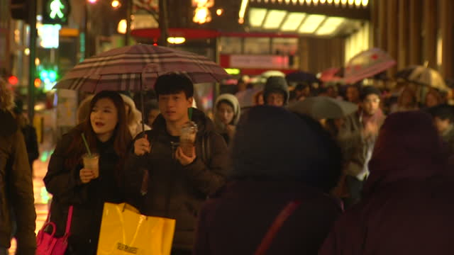 Exterior night shots people walking at Oxford Street in rainy weather Crowd of people shoppers walking on February 22 2015 in London England