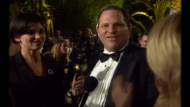 vídeos y material grabado en eventos de stock de exterior night shots producer harvey weinstein at oscars vanity party with wife eve chilton weinstein talking to press on 21 of march 1999 in los... - miramax