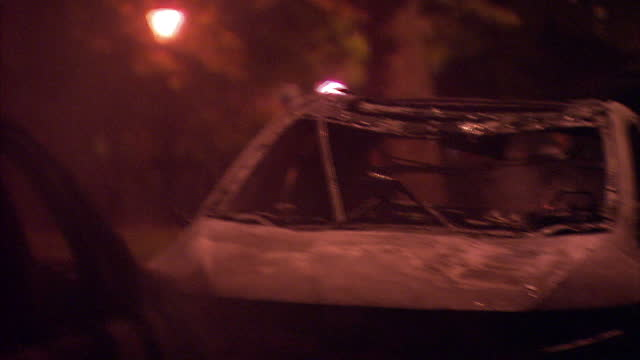 exterior night shots riot police spanning street. exterior shot riot policeman kicks out small fire on the street. exterior shotsburnt out cars... - littering stock videos & royalty-free footage