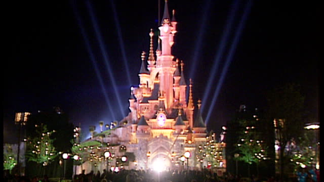 exterior night shots the disney sleeping beauty castle lit up with light beams on opening weekend of euro disney resort on april 11 1992 in paris... - disney stock videos and b-roll footage