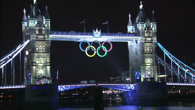 exterior night shots tower bridge lit up by light show with the olympic rings logo being highlighted by bright light tower bridge olympic rings light... - olympic rings stock videos & royalty-free footage