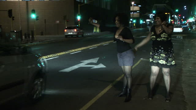 exterior night shots two prostitutes standing talking together on the side of the road waving down cars prostitutes working at night in johannesburg... - nutten stock-videos und b-roll-filmmaterial