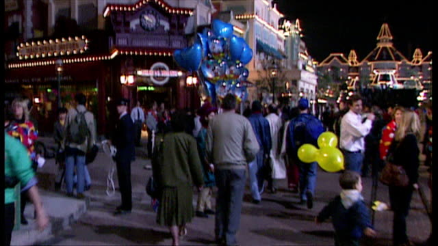 exterior night shots walking along 'main street usa' at euro disney resort on opening weekend with tourists walking around enjoying the park on april... - disney stock videos and b-roll footage