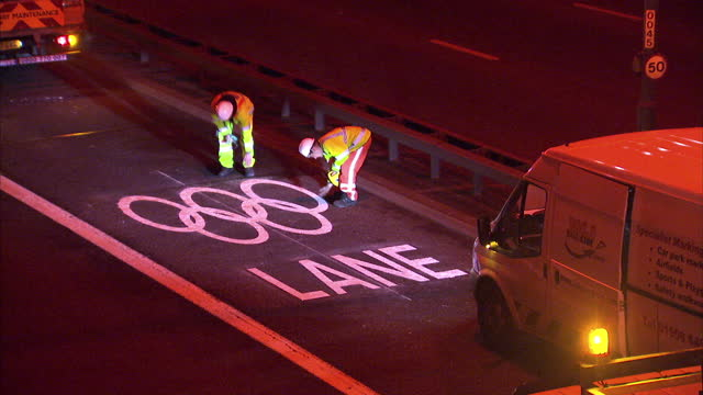 exterior night shots workmen painting olympic games logo on road using large stencil marker. exterior night shots workers working on olympic rings... - stencil stock videos & royalty-free footage