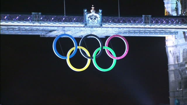 exterior night shotstower bridge lit up by light show highlighting the olympic rings logo hanging from its span tower bridge olympic logo light show... - 2012年ロンドン夏季オリンピック点の映像素材/bロール