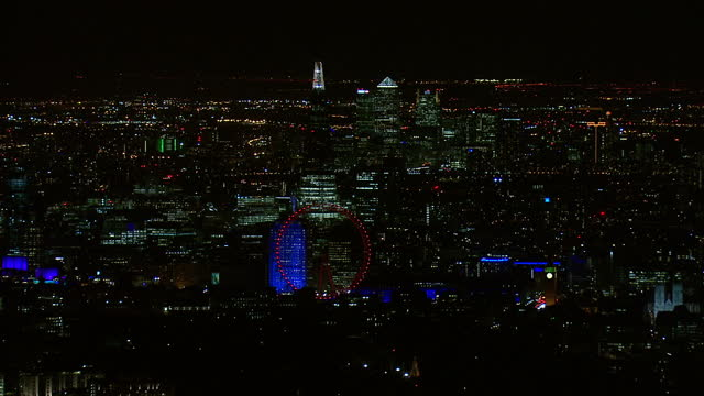 Exterior night time aerial shots of the City of London including the Shard London Eye illuminated in red and Canary Wharf on March 26 2015 in London...