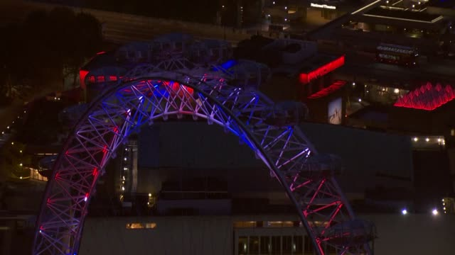 Exterior night time aerial shots of the London Eye observational wheel and nearby buildings lit up with red white and blue lighting to celebrate the...