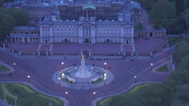Exterior night time aerial shots of The Mall Buckingham Palace and a small number of people gathered by the palace gates to celebrate the arrival of...