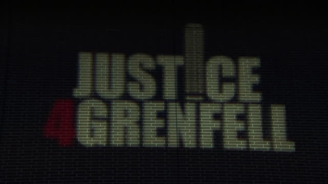 exterior night time shots of a tribute sign displayed and projected onto a building wall 'justice 4 grenfell' at a memorial to mark the one year... - トリビュート・イベント点の映像素材/bロール