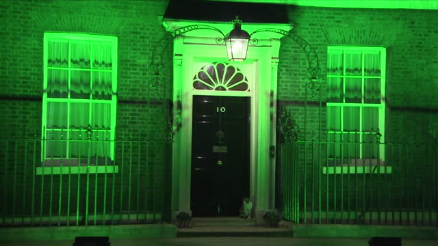 exterior night time shots of downing street switching on green lights in commemoration of the victims of the grenfell tower fire on the one year... - トリビュート・イベント点の映像素材/bロール