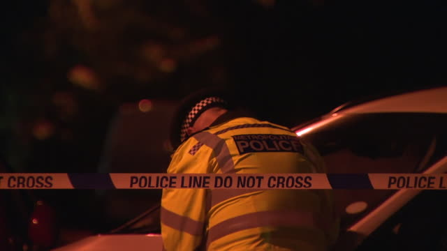 exterior night time shots of forensic police detectives searching crime scene next to police tape police car scene of the fatal stabbing of a... - murder stock videos & royalty-free footage