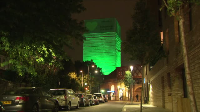 exterior night time shots of latimer road station including close up shots of grenfell tower wrapped in sheets and lit up in a green colour to mark... - トリビュート・イベント点の映像素材/bロール