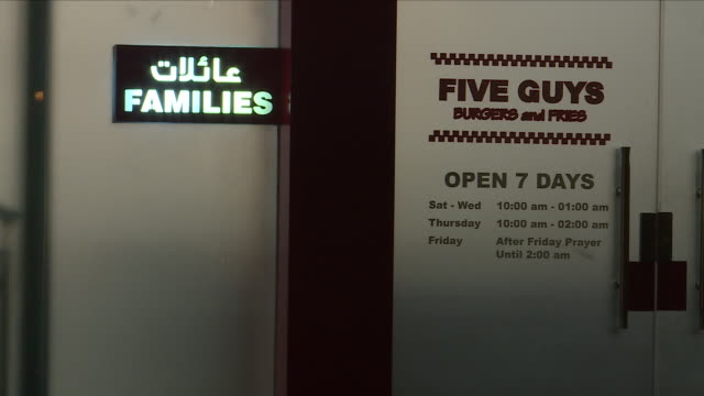 exterior night time shots of people walking in an restaurant and entertainment area of riyadh including a branch of the five guys burger chain with... - five people stock videos & royalty-free footage
