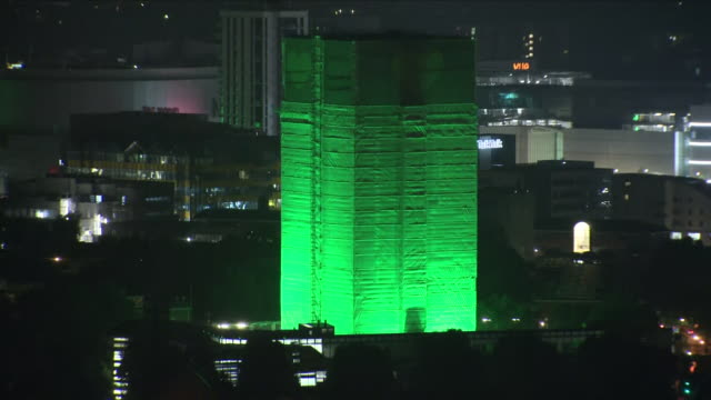 exterior night time shots of the wreckage of grenfell tower wrapped in sheets and lit up in bright green lighting to mark the one year anniversary of... - トリビュート・イベント点の映像素材/bロール