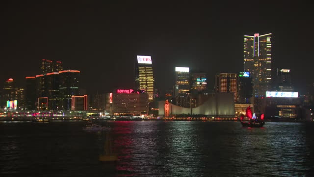 exterior night views of a hong kong junk boat sailing in the harbour and lit up in red light on 6 october 2019 in hong kong, china - dschunke stock-videos und b-roll-filmmaterial