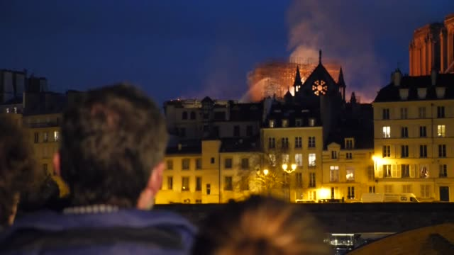 exterior night views of notre dame cathedral burning and engulfed by smoke as people watch from across the river seine on 15 april 2019 in paris,... - notre dame de paris stock videos & royalty-free footage