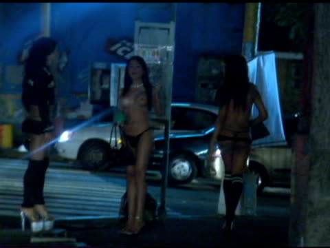 vídeos de stock, filmes e b-roll de exterior nightshots prostitutes working girls gathered on street corner wearing very skimpy clothing prostitutes on caracas street corner on february... - prostituta