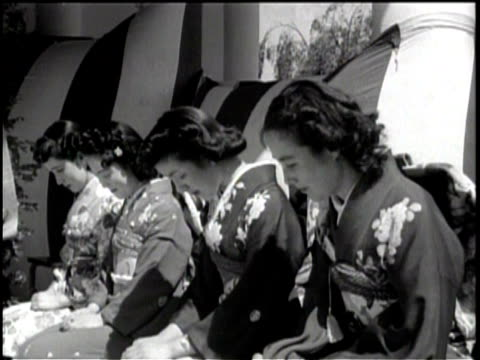 exterior of a stage pavilion / a group of asian women in traditional clothing sit with their heads bowed / a woman carries a lit candle and bows... - パビリオン点の映像素材/bロール