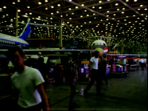 exterior of airplane on tarmac, plane has scaffolding surrounding it / interior of hanger showing rows of airplane wings / workers on airplane wing /... - 飛行機格納庫点の映像素材/bロール