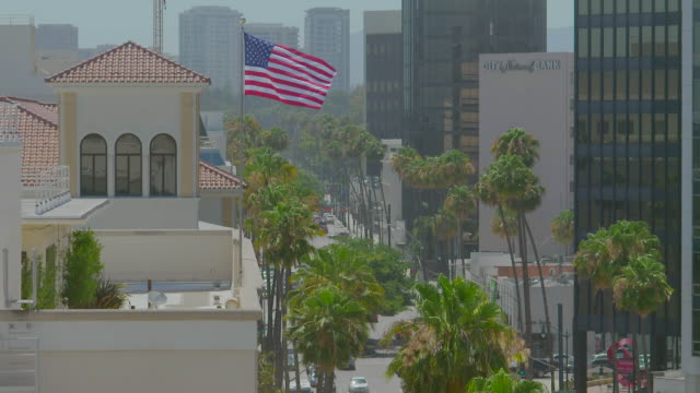 ws exterior of beverly wilshire hotel with american flag waving in foreground / beverly hills, los angeles county, california, united states - beverly hills hotel stock videos and b-roll footage