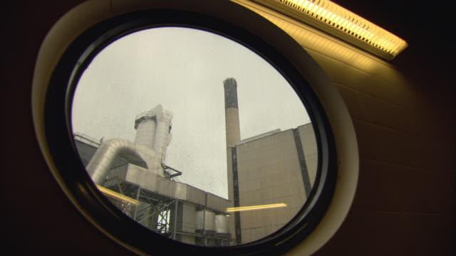 ws la exterior of biomass plant factory seen through circular window / vaxjo, sweden - vaxjo stock videos & royalty-free footage