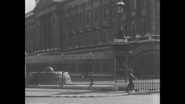 exterior of buckingham palace mermaid statues at base of victoria memorial in front of palace in foreground / royal foot guard walking along fence... - black and white stock videos & royalty-free footage
