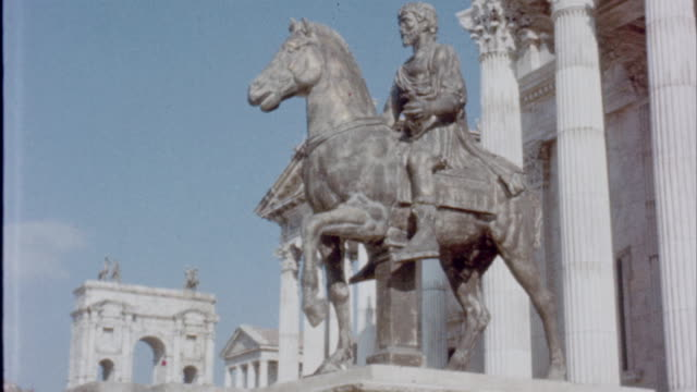 vídeos de stock e filmes b-roll de exterior of building with man on horse statue / roman soldiers marching slaves down street / roman citizens walking up and down stairs recreation of... - the machine: master or slave
