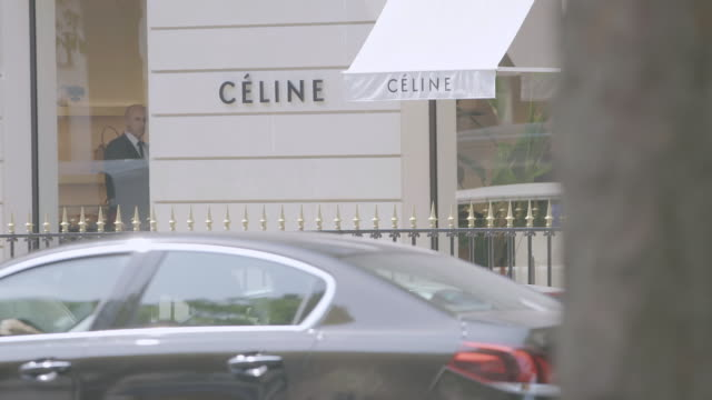 MS Exterior of Celine shop, cars moving on road in foreground / Paris, France