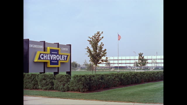 vidéos et rushes de ws exterior of chevrolet building, american flag waving in background / united states - chevrolet