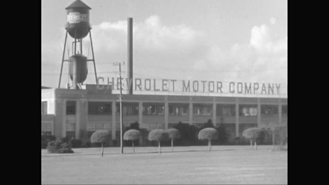 ws pan exterior of chevrolet motor company of california with water tower / california, united states - storage tank stock videos and b-roll footage