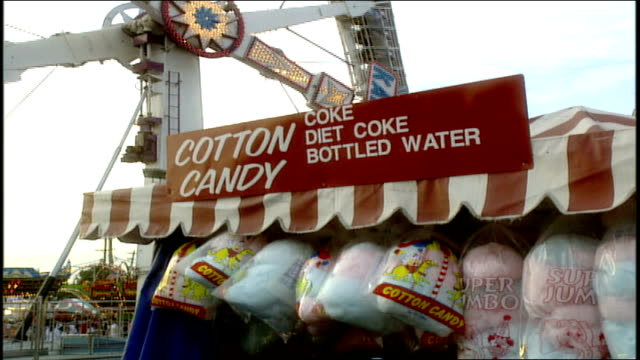 exterior of cotton candy stand at carnival with ride in background - fiesta background stock videos & royalty-free footage