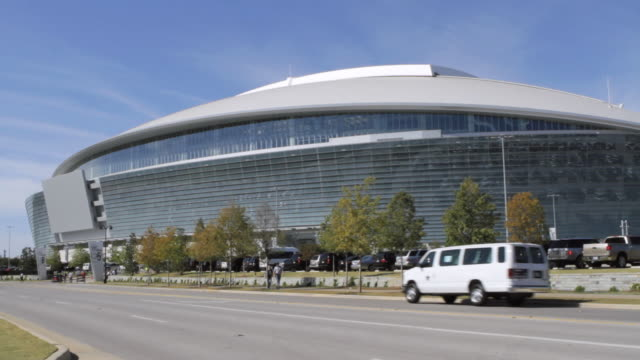 pan exterior of cowboys stadium arena from across a street / arlington, texas, united states - telecamera traballante video stock e b–roll