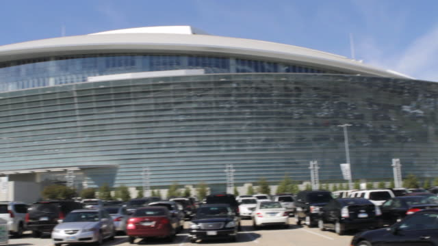 pan exterior of cowboys stadium arena from crowded parking lot / arlington, texas, united states - sportliga stock-videos und b-roll-filmmaterial