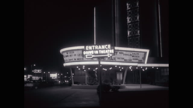 ws exterior of drive-in theatre with vehicles moving on street at night / united states - theater marquee commercial sign stock videos & royalty-free footage