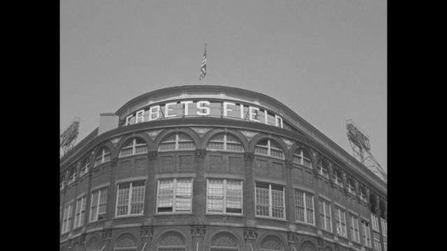 VS exterior of Ebbets Field in New York City with people traffic tilt ÒEbbets FieldÓ with American flag to street with traffic people walking to the...