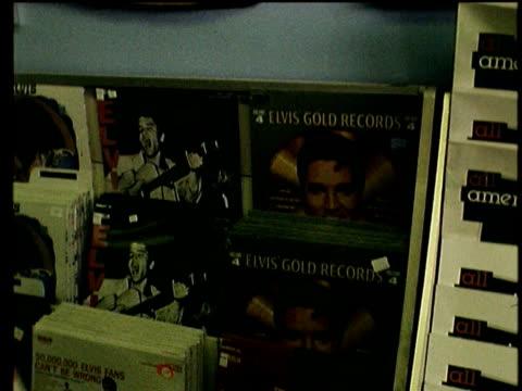 vídeos y material grabado en eventos de stock de exterior of elvis presley souvenir shop / shoppers inside elvis souvenir shop / views of elvis records books framed photographs memorabilia first... - tienda de discos