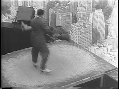 vídeos de stock, filmes e b-roll de exterior of empire state building / skaters performing on top of empire state building / earl and jack of the skating earls perform dizzying spins on... - ponto de observação
