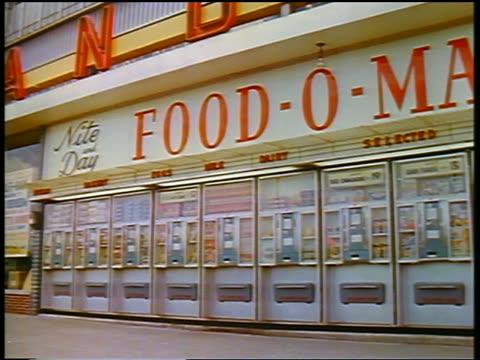 vídeos de stock, filmes e b-roll de 1957 pan exterior of food-o-mat (wall of automatic food vending machines) - 1957