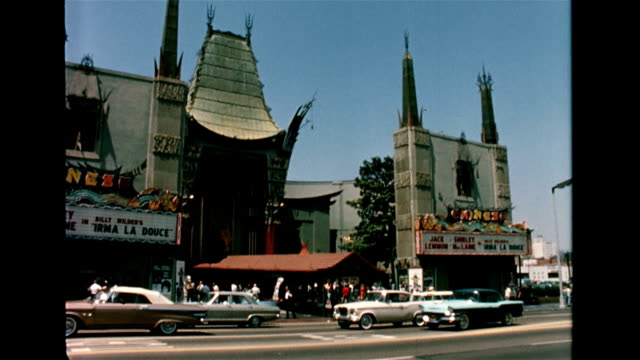 / exterior of Grauman's Chinese Theater / crowd in front of theater looking at star's hand prints in the cement / tourists putting hands into hand...